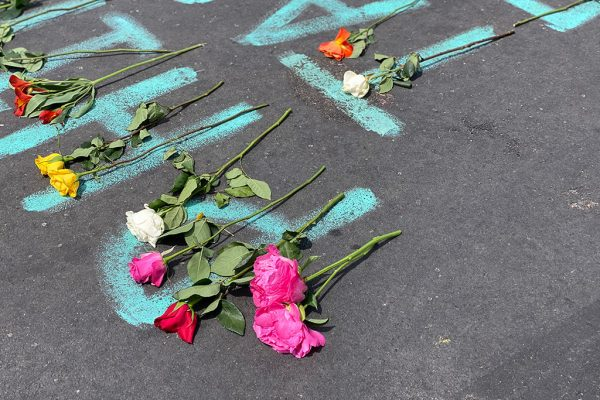 Flowers sit on top of names on the street in Minneapolis.